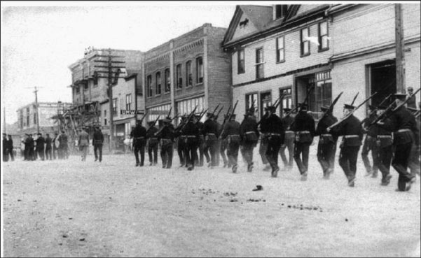 Militia Marching on First (1st) Avenue., circa 1913. Buildings in the photo include the Travellers Hotel, 512 1st Avenue, (Ladysmith Archives collection)