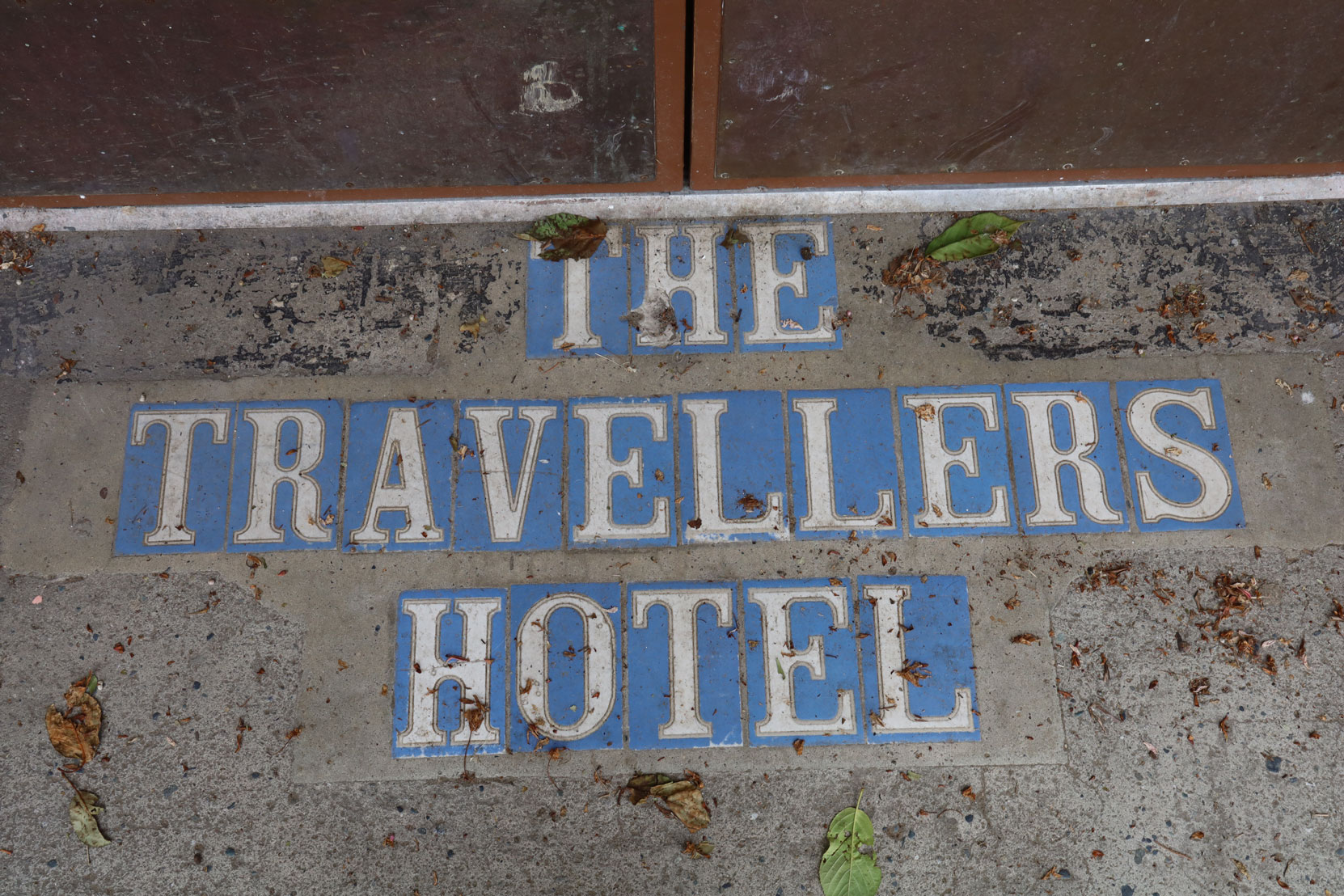Tile sign at the entrance to the Travellers Hotel, 422 1st Avenue.